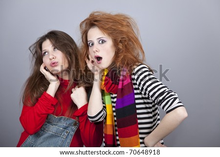 Two funny girls. One of them calling by phone.  Studio shot. - stock photo
