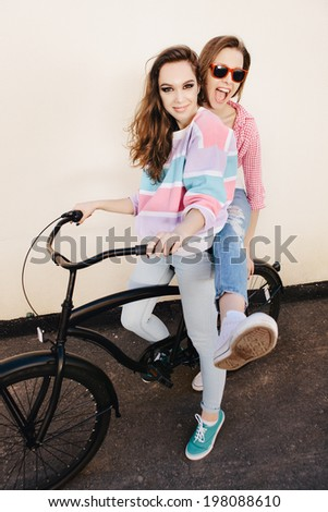 Two funny girls with bicycle having fun. Outdoors, lifestyle.