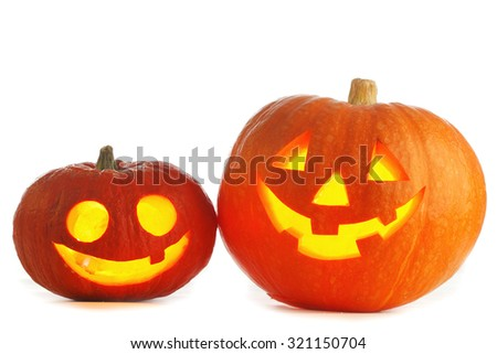Two funny Halloween Jack O' Lantern pumpkins on black background - stock photo