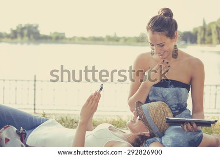 Two funny happy young women friends laughing browsing sharing watching social media videos blogs on smart phone pad computer laying outdoors on green meadow on sunny summer day  - stock photo