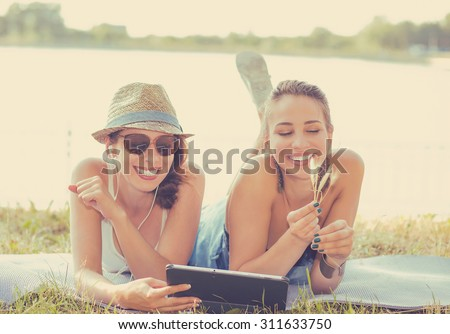 Two funny happy young women friends laughing browsing sharing watching social media videos blogs on pad computer laying outdoors on green meadow on sunny summer day - stock photo