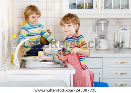 Two funny little boy friends washing dishes in domestic kitchen. Children having fun with helping with housework. Indoors, kids in colorful clothes. Selective focus