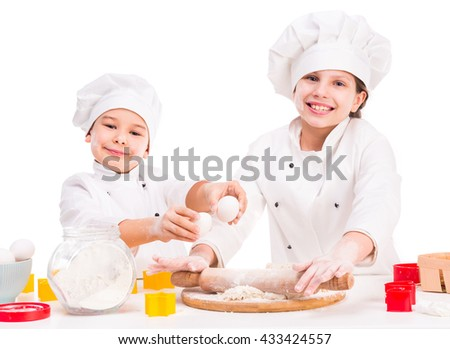 two funny little cooks in white uniform preparing dough in the kitchen