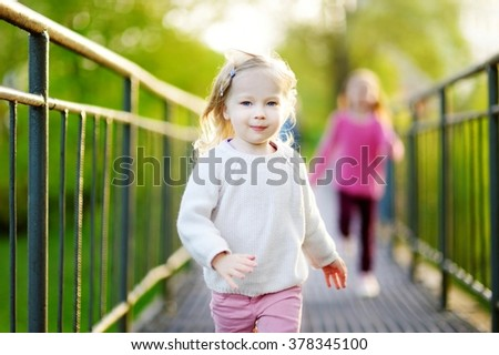 Two funny little girl jumping and running with joy and happiness outdoors on beautiful summer day - stock photo