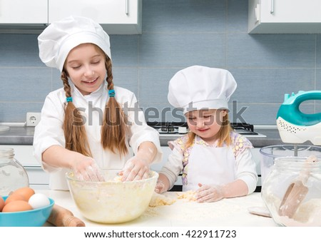 two funny little girls in chef uniform knead the dough on kitchen table