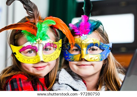 Two funny little girls with masks - stock photo