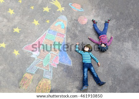 Two Funny little kid boys flying in universe by a space shuttle picture painting with colorful chalks. Creative leisure for children outdoors in summer. Friends having fun together