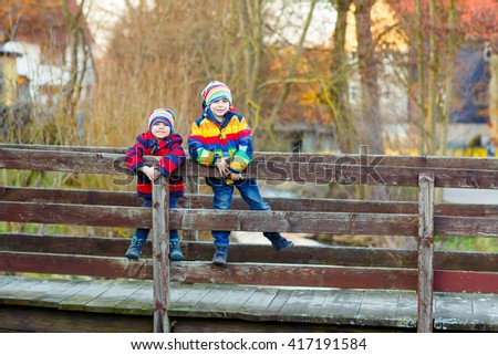 Two funny little kid sibling boys and friends in colorful clothes standing on bridge on spring day. Children having fun together, autumn or spring. Happy, joyful family - stock photo