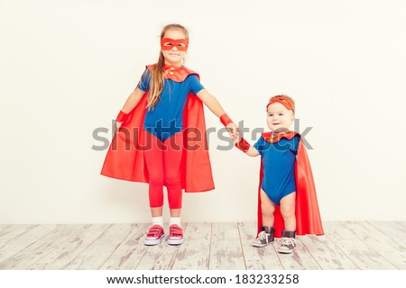 Two funny little power super hero kids in a blue raincoat. Superhero concept - stock photo
