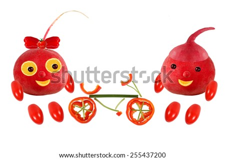 Two funny little radish standing with bicycle. The picture is made from fruit and vegetables - stock photo