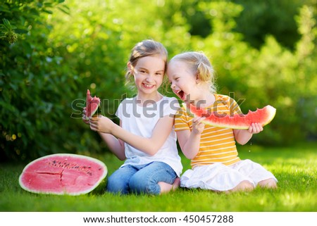 Two funny little sisters eating watermelon outdoors on warm and sunny summer day - stock photo
