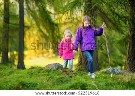 Two funny little sisters having fun during forest hike on beautiful autumn day in Italian Alps