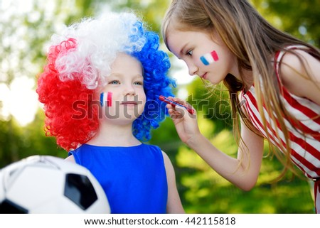 Two funny little sisters supporting and cheering their national football team during soccer championship - stock photo
