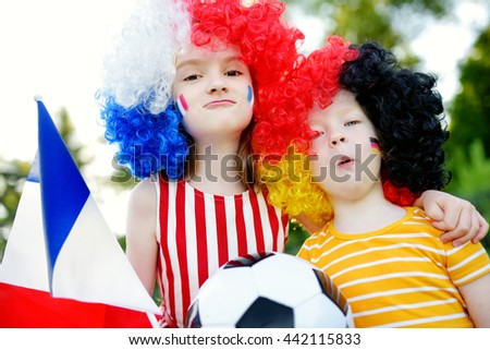 Two funny little sisters supporting and cheering their national football teams during soccer championship