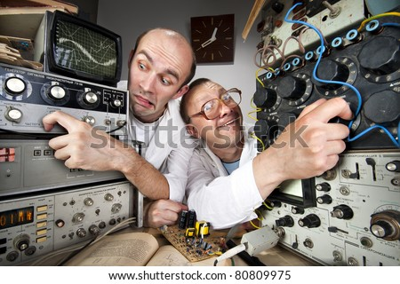 Two funny nerd scientists working at vintage technological laboratory