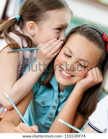 Two funny schoolgirls whisper to each other - stock photo