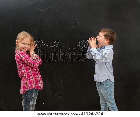 two funny shoolchildren talking on self-made drawn on the blackboard telephone - stock photo