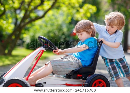 Two funny twins boys having fun with toy race car in summer garden, outdoors. Adorable brother pushing the car with another child. Outdoor games for children in summer concept.