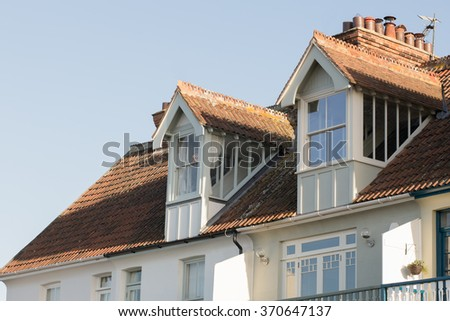 Two gabled dormer windows on terrace, row houses, in Whitstable, UK England.  Rooftop.