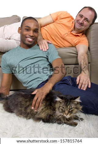 two gay lovers relaxing at home in the livingroom - stock photo