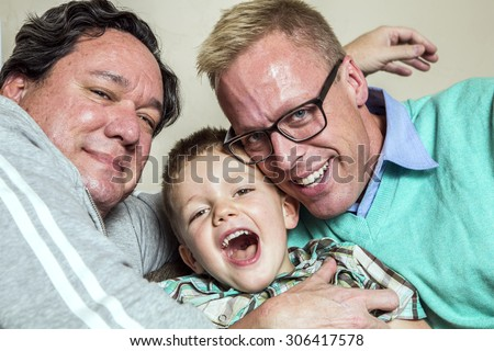 Two gay men hug their happy young son - stock photo