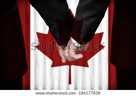 Two gay men stand hand in hand before a marriage altar featuring an overlay of the flag colors of Canada, having just been legally married under the Same-Sex Marriage legislation of that country.  - stock photo