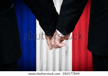 Two gay men stand hand in hand before a marriage altar featuring an overlay of the flag colors of France, having just been legally married under the Same-Sex Marriage legislation of that country.