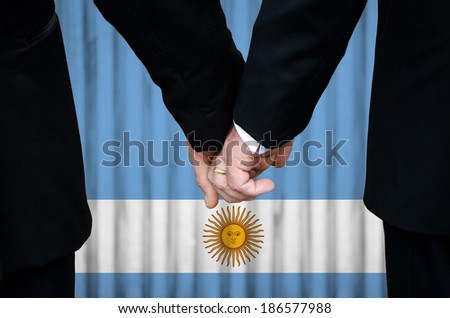 Two gay men stand hand in hand before a marriage altar featuring an overlay of the flag colors of Argentina, having just been legally married under the Same-Sex Marriage legislation of that country.  - stock photo