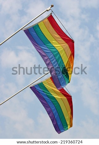 Two gay pride flags waving in the wind - stock photo