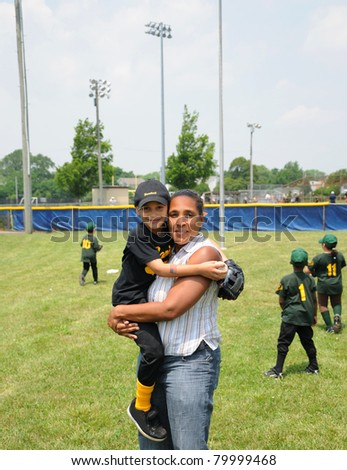Two Generation Family Boy wearing Uniform in arms of Grandmother on Baseball Practice Field - stock photo