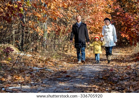 Two Generation Family Walking in Autumnal Forest Alley Father Mother Holding Hands of Little Baby Girl Bright Yellow Clothing Coat and Cap Front View