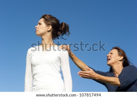 Two  generations, mother and daughter in conflict, fighting, communicating. With one arm and finger pointing towards young girl. Isolated with blue sky as background and copy space.