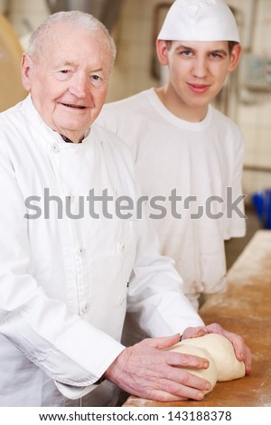 Two generations of bakers at work in the bakery - stock photo
