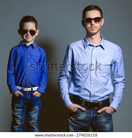 Two gentlemen: young father and his little cute son in sunglasses. Are dressed in shirts and jeans. Studio shot - stock photo