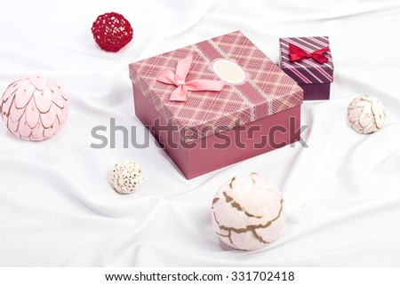 Two gift boxes on white satin background with ball decorations - stock photo