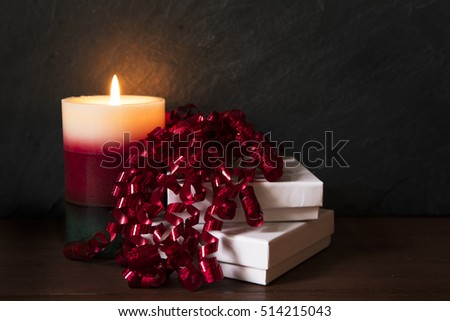 Two gift boxes with curly red ribbon and festive candle.