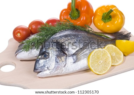Two gilt-head fishes with vegetables on a cutting board isolated over white - stock photo