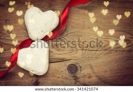Two gingerbread heart shape in white glaze on old table - stock photo
