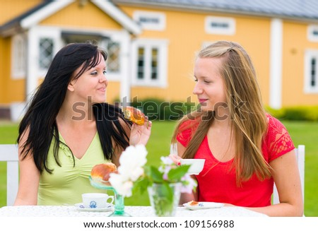 Two girl friends have a good time together on coffee table