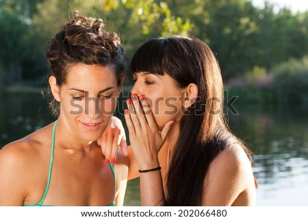 Two girl friends in bikini gossiping near a river in summer holidays - stock photo