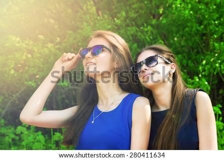 Two girl friends in blue sunglasses and looking to the side on a green background - stock photo
