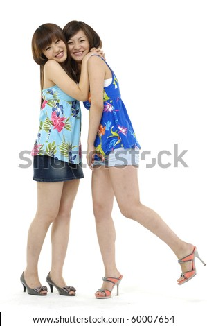 Two girl friends in full length together smiling. Studio shot. - stock photo
