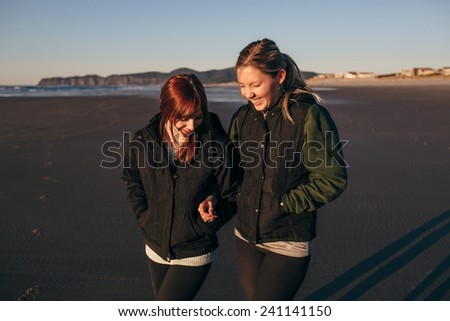 Two Girl Friends on the Beach Laughing and Walking - stock photo