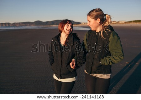 Two Girl Friends on the Beach Laughing with Each other and Walking at Sunset closer - stock photo