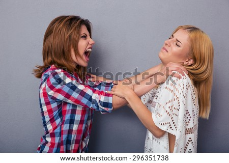Two girl friends quarrel over gray background