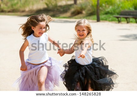 Two girl friends running together holding hands in park. - stock photo