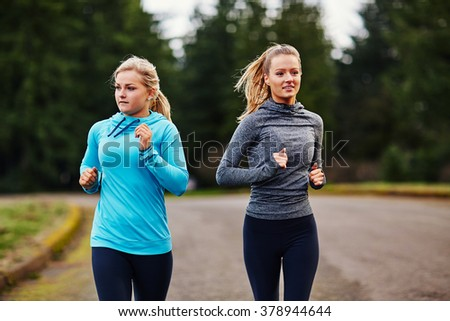 two girl friends running together looking opposite direction - stock photo