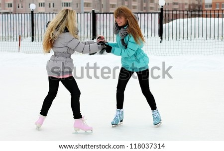 Two girl friends skating on a lake together - stock photo