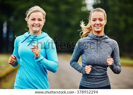 two girl friends smiling and running together