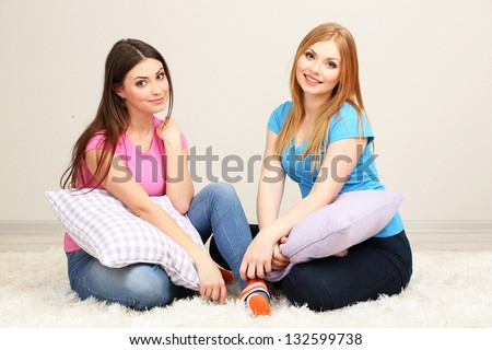 Two girl friends smiling on room